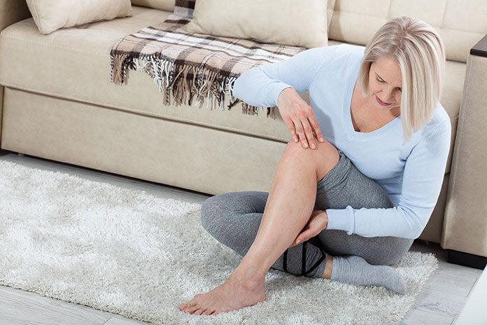Skurcz łydki - kobieta siedząca na dywanie i trzymająca się za bolącą łydkę