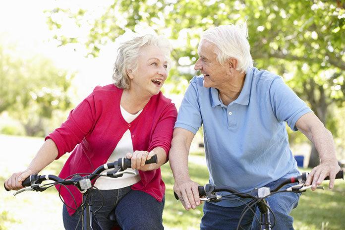 Aktywność fizyczna osób starszych - para uśmiechniętych seniorów podczas jazdy na rowerach